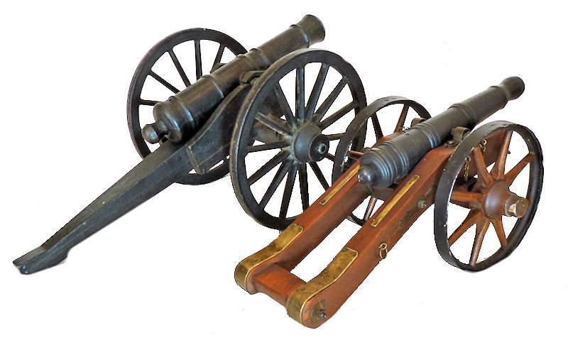 The giant Revolutionar War cast iron cannon shown next to a smaller wood and iron field cannon of                                     the same period image