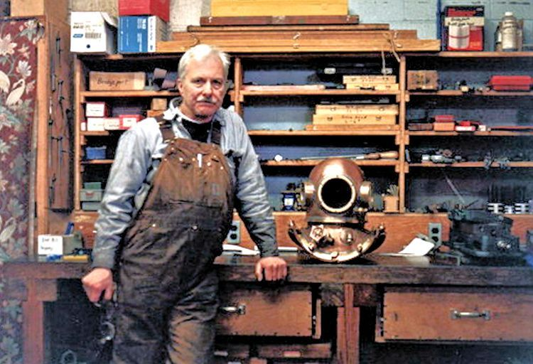 David L. Clark in                                     his shop alongside one of his copper dive hellmets image